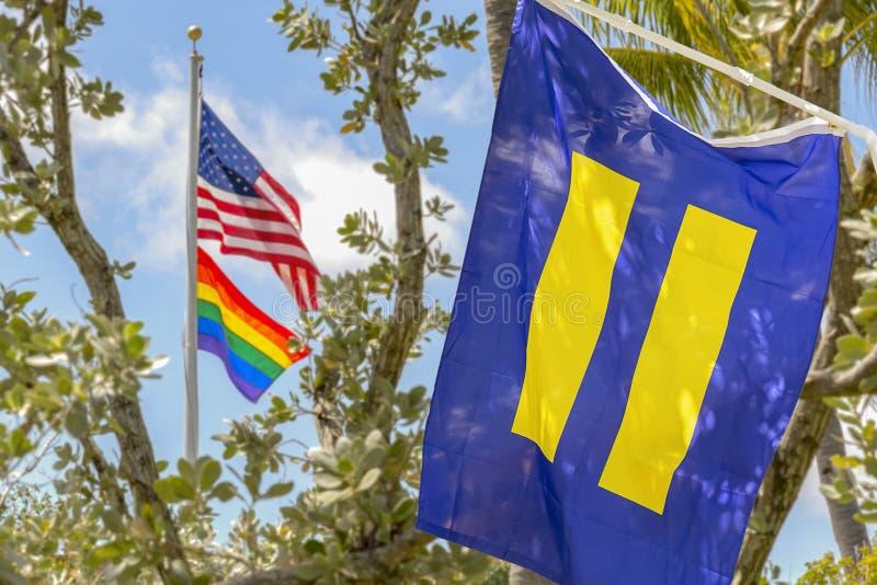 美国国旗飞行高与同性恋自豪日和平等旗子 免版税图库摄影