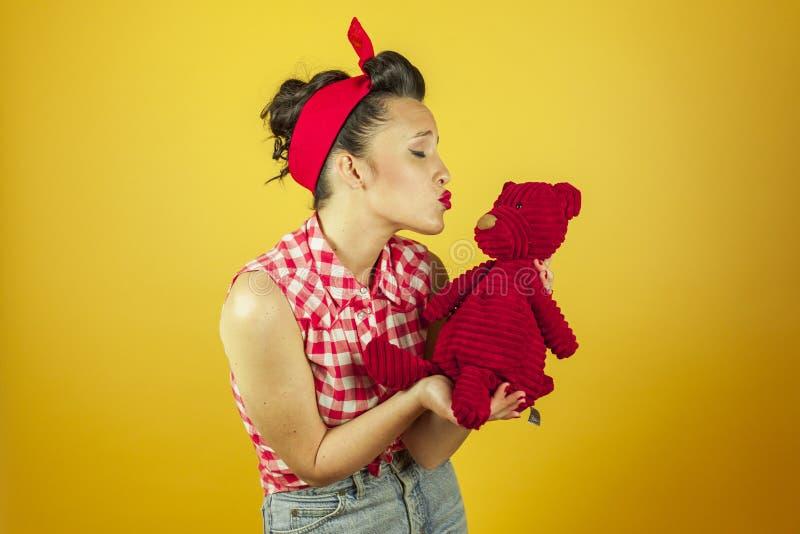 美国射击画象美丽的别针与逗人喜爱的红色玩具熊 图库摄影