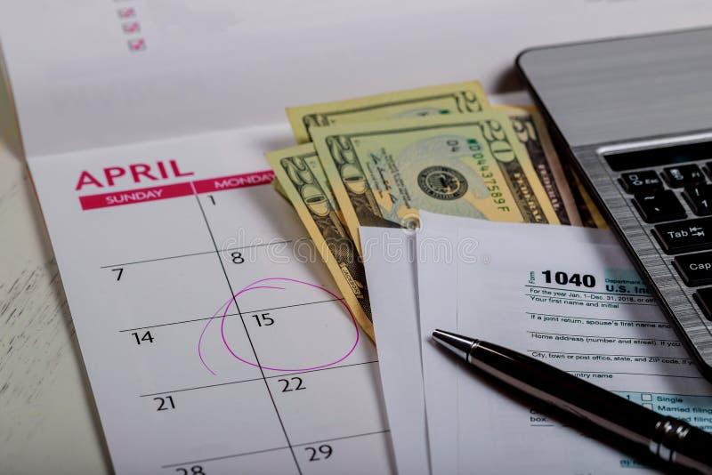 1040美国报税表、金钱和日历与U S美元金钱和计算机 免版税库存照片