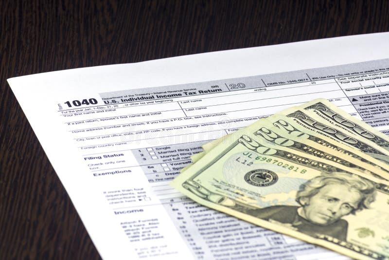 美国报税表1040在桌上 一些张票据在上面 20和100美元现金  免版税库存照片