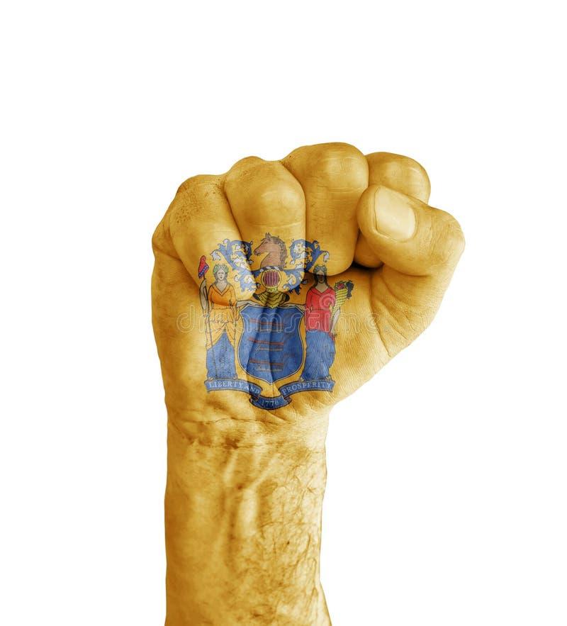 美国新泽西状态旗子在人的拳头绘的喜欢胜利 库存图片