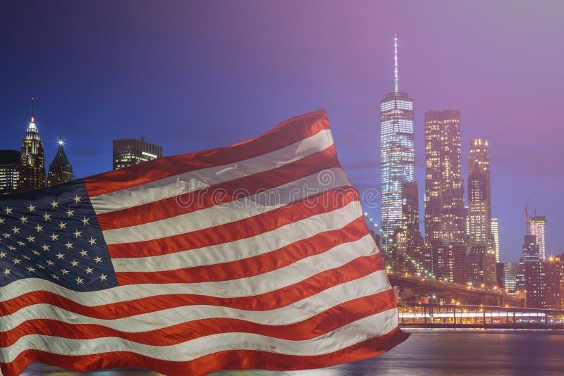 美国旗子纽约& x27; s布鲁克林大桥和被阐明的曼哈顿地平线 免版税库存照片