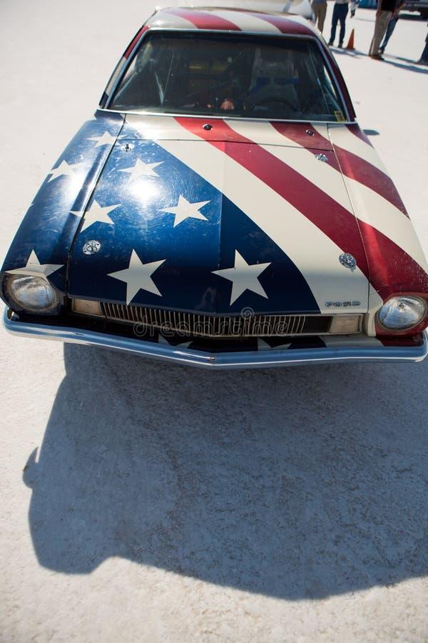 美国旧车改装的高速马力汽车的前方有被绘的美国国旗的  图库摄影