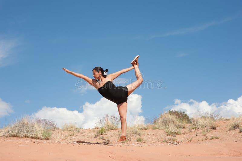 美国本地人弓姿势的瑜伽妇女 免版税库存图片