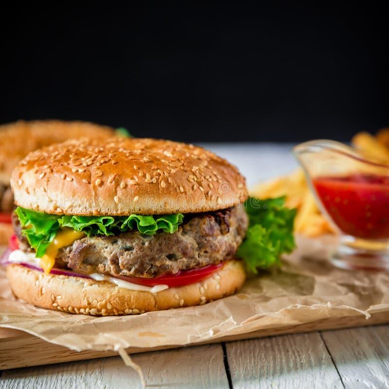美国汉堡包用牛肉、炸薯条和西红柿酱在黑暗的背景 免版税图库摄影