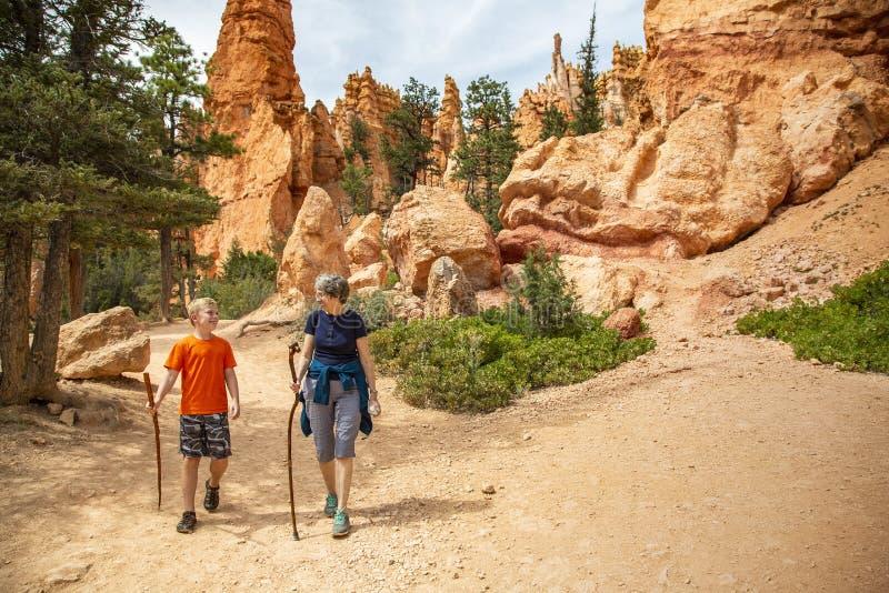 美国犹他州布莱斯峡谷国家公园的资深女性和孙子一起远足,眺望风景优美的景色 免版税库存照片