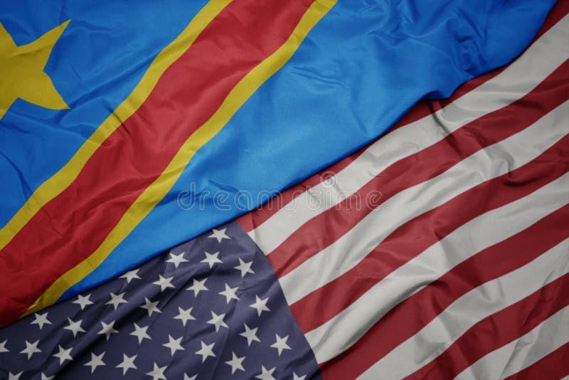 美国的挥动的五颜六色的旗子和刚果民主共和国的国旗 库存照片