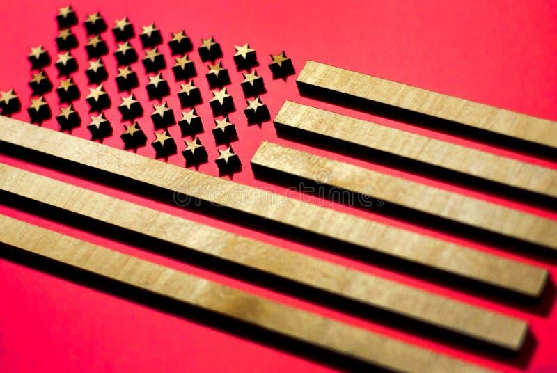 美国的旗子红色背景的由木头,在红色背景的金黄条纹制成 库存照片