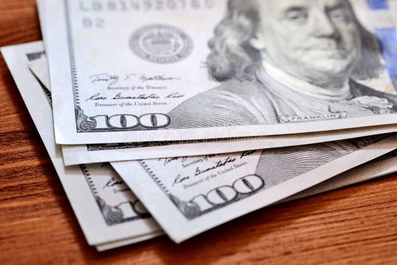 美国美元在木桌上的钞票 免版税库存图片