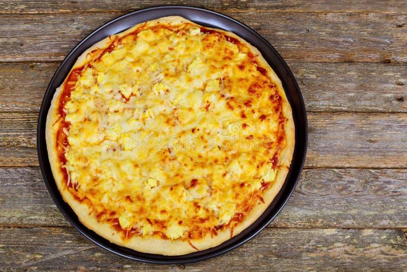 美国薄饼用意大利辣味香肠、无盐干酪和西红柿酱 在一张木桌上的薄饼, 免版税库存图片
