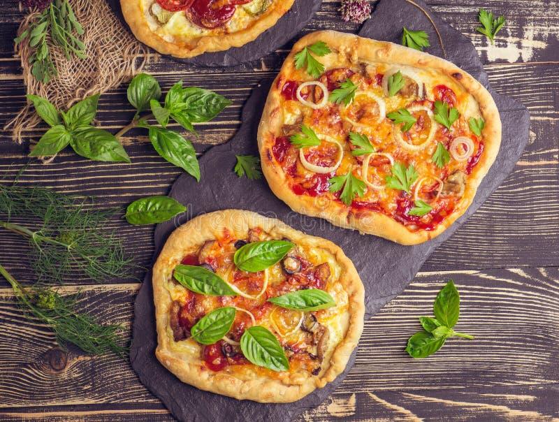 美国薄饼用无盐干酪,蕃茄,在黑暗的木桌上的意大利辣味香肠 免版税库存图片