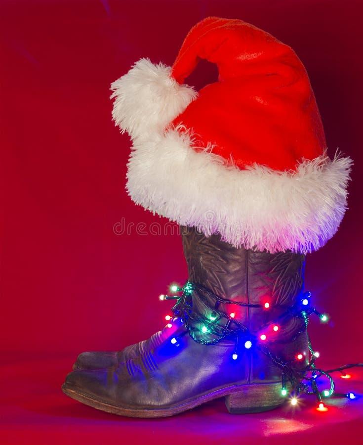 美国西部传统靴子和圣诞老人帽子在圣诞节红色b 免版税库存照片