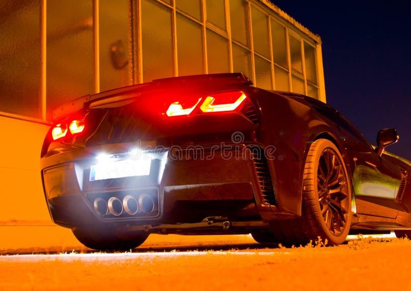 美国跑车在与发光的尾灯的晚上 库存照片