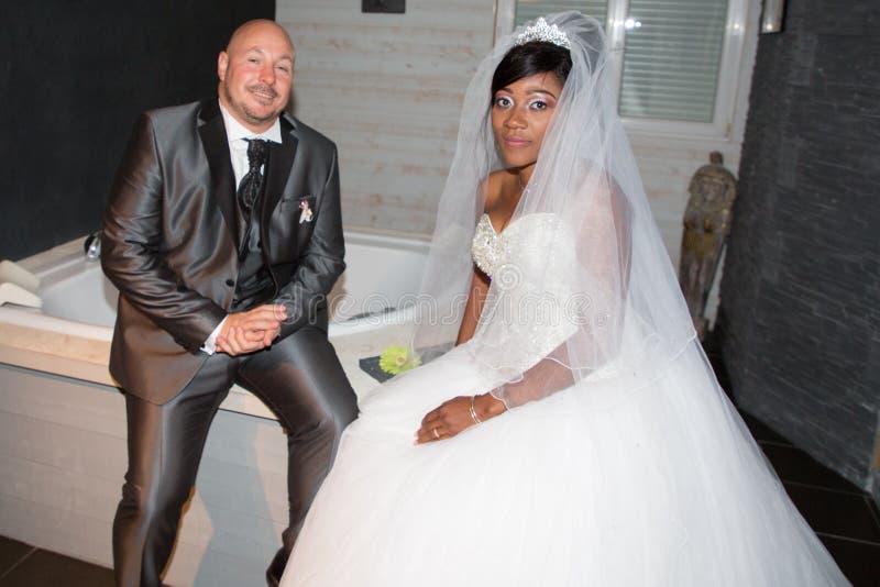 美国非洲人mixed-race夫妇结婚的新娘和新郎在家 库存照片