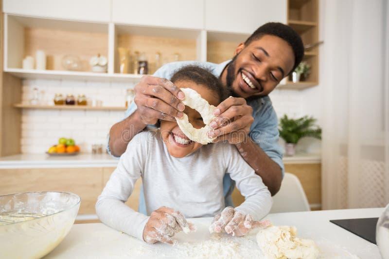美国黑人的一起烹调酥皮点心的人和女孩 免版税库存图片