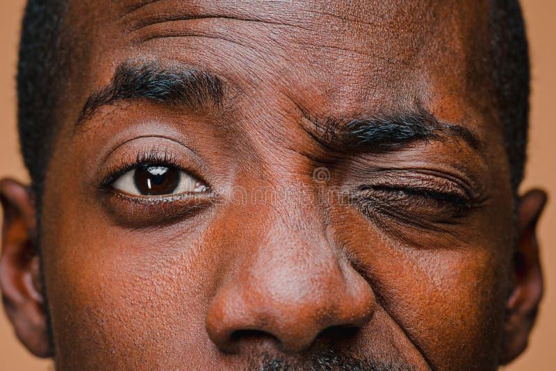 美国黑人的时髦的人半眯着的眼睛棕色演播室墙壁的 免版税库存照片