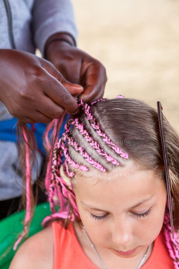 美国黑人的美发师做了在非洲样式的稀薄的桃红色褶年轻白种人女孩的 免版税库存照片