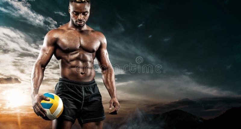 美国黑人的运动员,有一个球的沙滩排球球员画象在天空背景 适合的年轻人  免版税库存照片