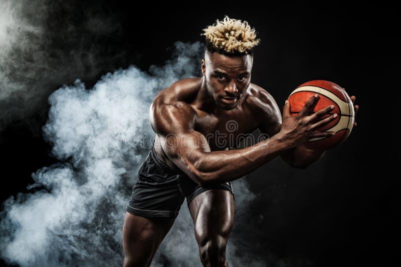美国黑人的运动员,有一个球的蓝球运动员画象在黑背景 运动服的适合的年轻人 库存照片