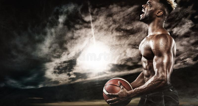 美国黑人的运动员,有球的蓝球运动员画象  拿着球的运动服的适合的年轻人 图库摄影