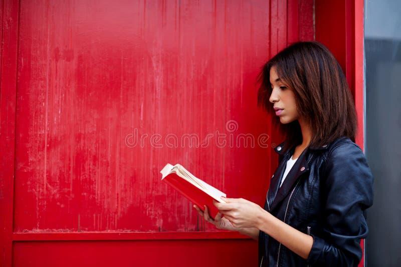 美国黑人的妇女读了文学,当站立户外时 免版税库存图片