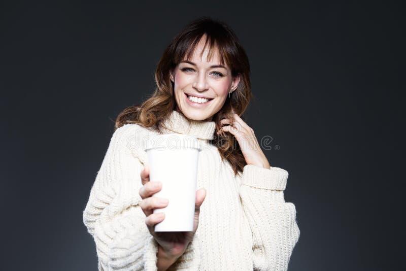 美女佩带的毛线衣拿着纸一次性咖啡杯 饮用的咖啡,微笑和笑 免版税库存照片