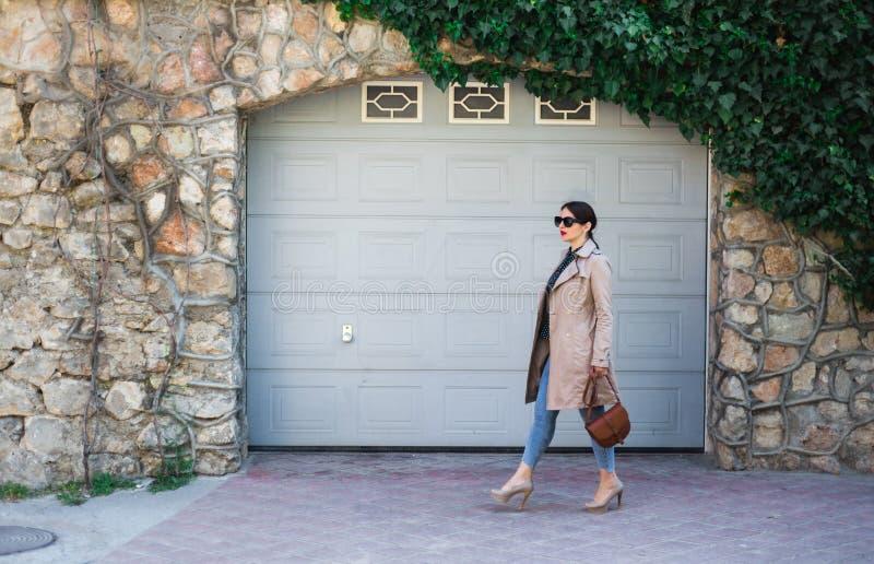 美女佩带的牛仔裤和沟槽,站立对在城市街道上的墙壁 偶然时尚,典雅的每天神色 免版税库存图片