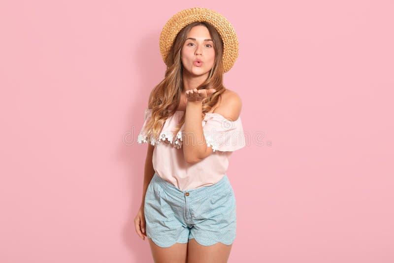 美女佩带的草帽,女衬衫,短小接近的画象,站立微笑和吹的空气亲吻直接地在照相机 免版税库存照片