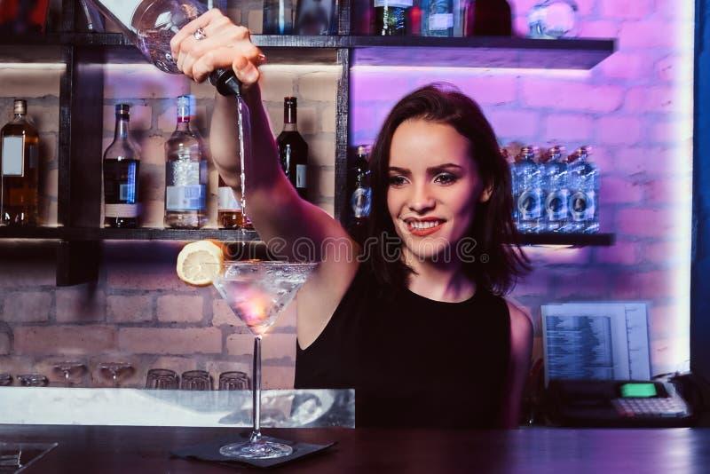 美女侍酒者准备一个酒精鸡尾酒用伏特加酒 免版税库存图片