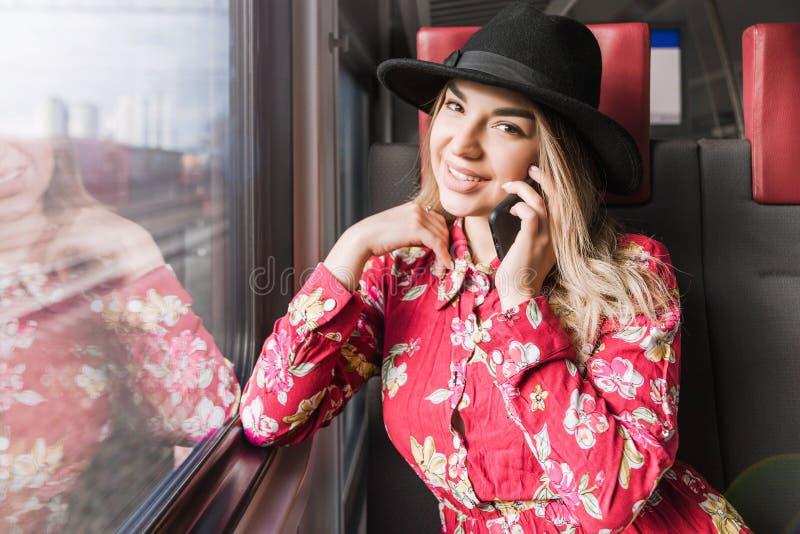 美女单独坐在火车和谈话在一个手机 免版税图库摄影