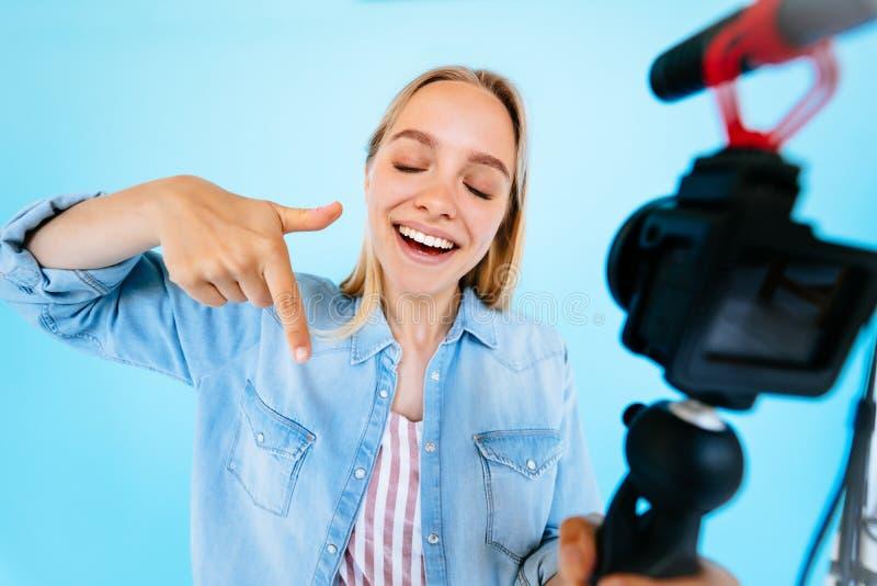 美女博客作者解除自己在照相机被隔绝的蓝色背景 免版税库存照片