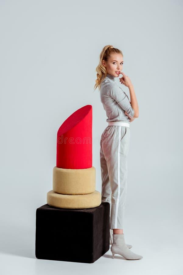 美女咬住的手指和摆在大红色口红模型附近 免版税库存照片