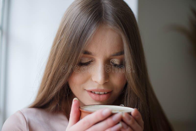 美女喝着坐在咖啡馆的咖啡和微笑的一会儿 免版税库存图片