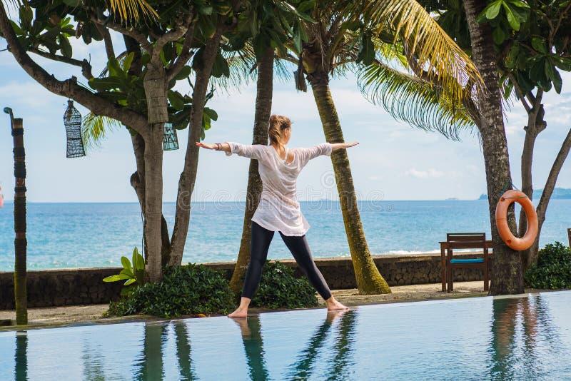美女在印度尼西亚实践瑜伽,凝思,站立从后面的姿势在与海洋风景的手段  免版税图库摄影