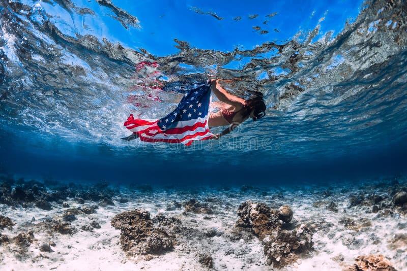 美女在含沙海底的freediver游泳与美国旗子 图库摄影