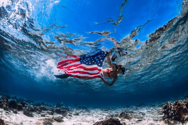 美女在含沙海底的freediver游泳与美国旗子 库存图片