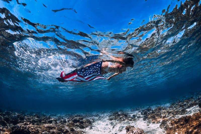 美女在含沙海底的freediver游泳与美国旗子 免版税库存照片