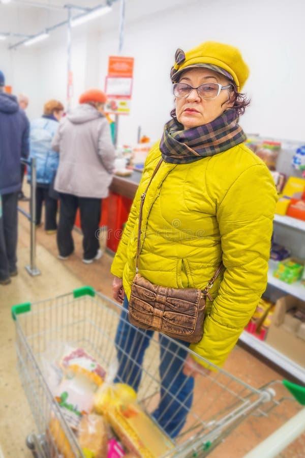 美女在商店选择泡泡糖和甜点 免版税图库摄影