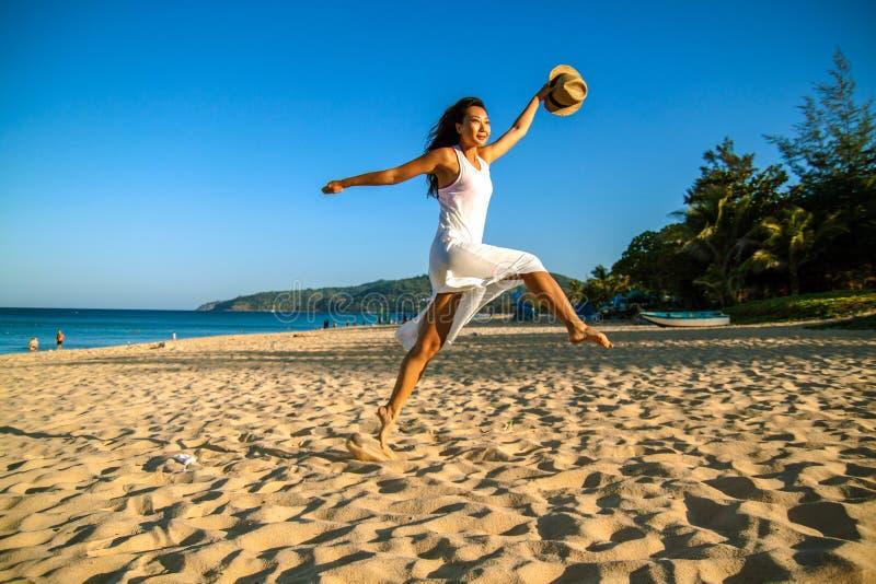 海滩微笑的亚裔妇女愉快 美女在夏天海滩的白色户外 库存图片