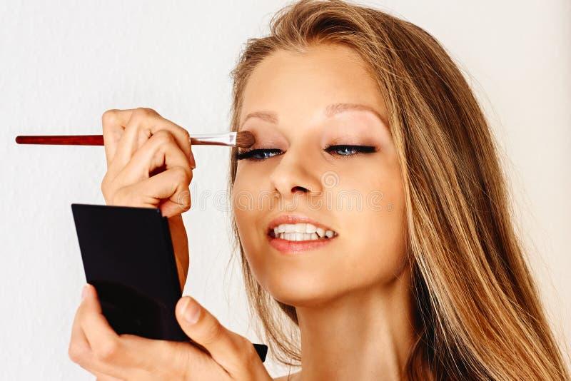 美女在她的面孔上拿着构成刷子并且把化妆用品放 组成,化妆用品,秀丽,眼睛鞭子引伸 图库摄影