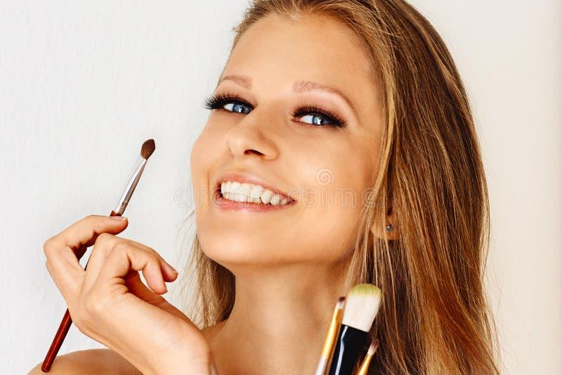 美女在她的面孔上拿着构成刷子并且把化妆用品放 组成,化妆用品,秀丽,眼睛鞭子引伸 免版税图库摄影