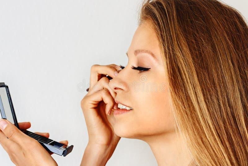 美女在她的面孔上拿着构成刷子并且把化妆用品放 组成,化妆用品,秀丽,眼睛鞭子引伸 免版税库存图片