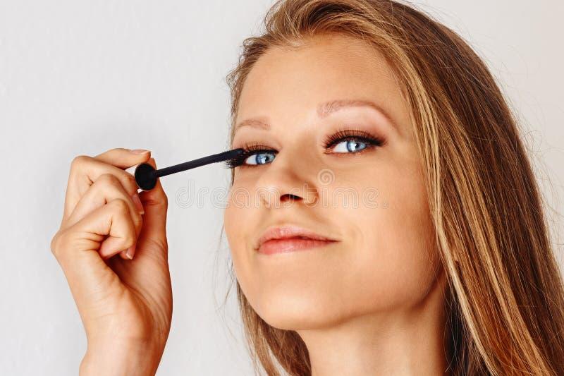 美女在她的面孔上拿着染睫毛油刷子并且把化妆用品放 构成,化妆用品,秀丽,眼睛鞭子引伸 免版税库存照片