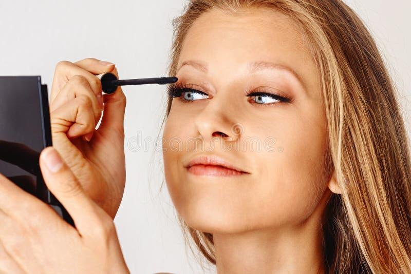 美女在她的面孔上拿着染睫毛油刷子并且把化妆用品放 构成,化妆用品,秀丽,眼睛鞭子引伸 免版税库存图片