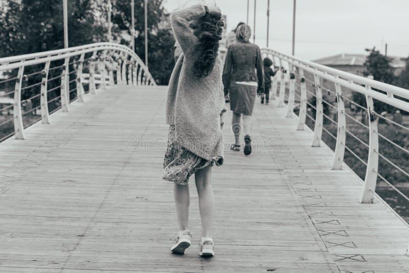 美女在桥梁在她的面孔站立,风吹,发展她的头发 女孩微笑 跳舞的黑白照片 图库摄影