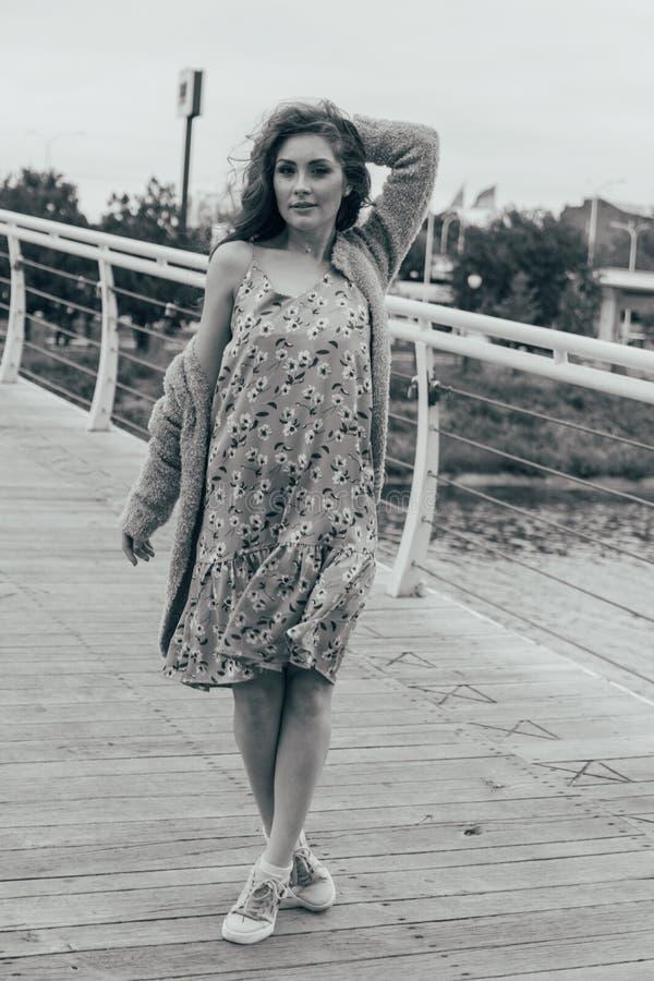 美女在桥梁在她的面孔站立,风吹,发展她的头发 女孩微笑 跳舞的黑白照片 库存照片