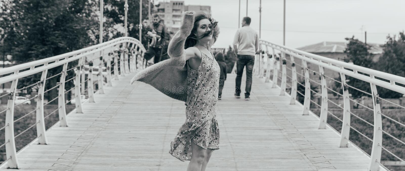 美女在桥梁在她的面孔站立,风吹,发展她的头发 女孩微笑 跳舞的黑白照片 库存图片