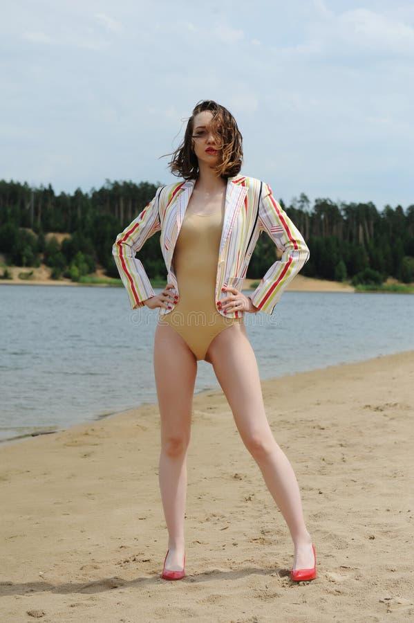 美女在海滩的时装模特儿在泳装、夹克和红色被停顿的鞋子 在头发的风 时髦的图象 免版税库存图片