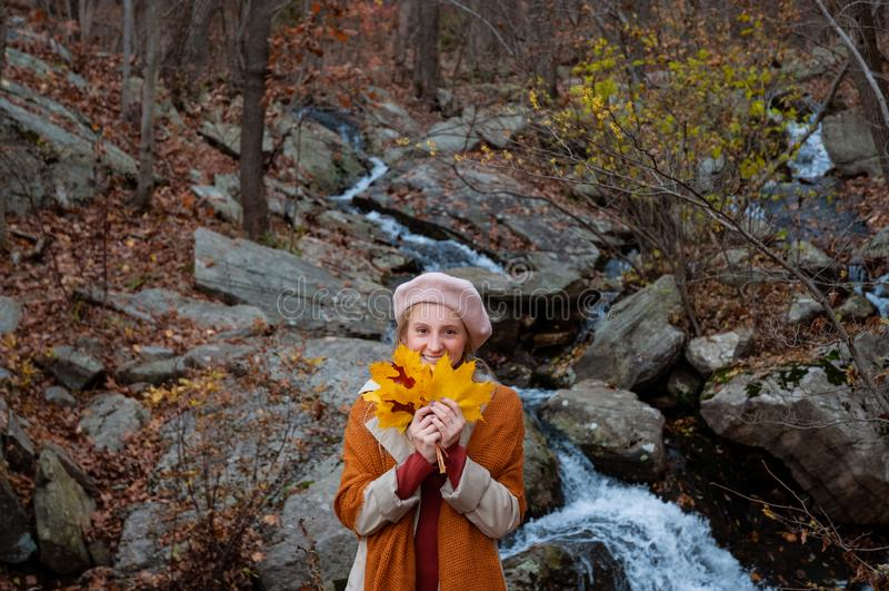 美女在秋天在有黄色叶子的公园,微笑和享受自然 汽车城市概念都伯林映射小的旅行 免版税库存照片
