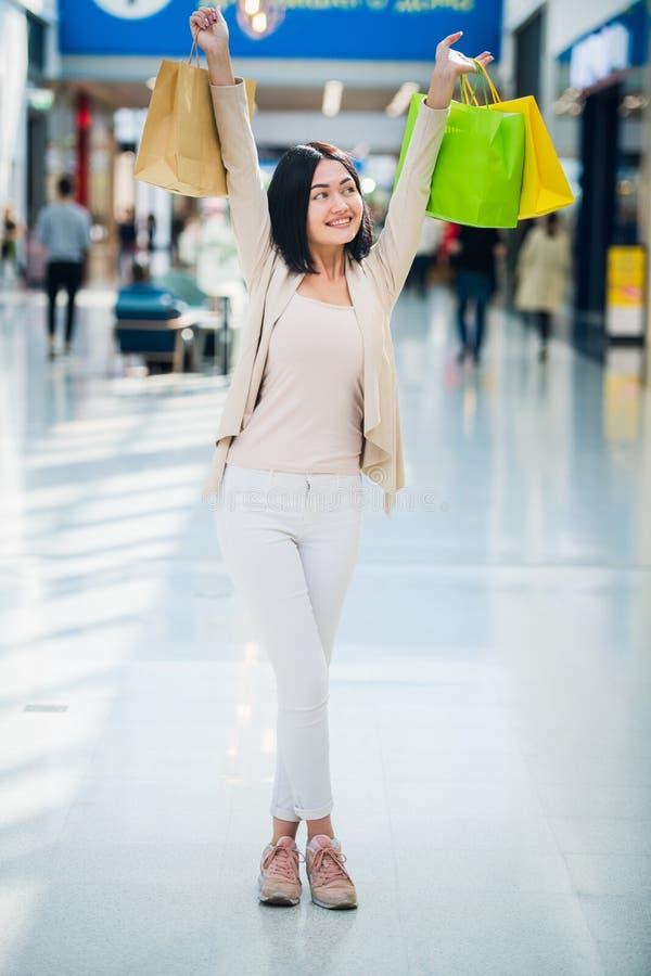 美女在购物中心,看照相机,广泛微笑和在被举的手上拿着五颜六色的购物带来 免版税库存照片